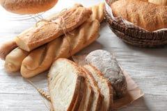 Olikt nytt smakligt bröd på den vita trätabellen arkivbild