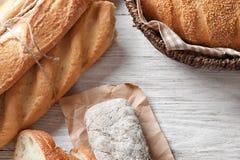 Olikt nytt smakligt bröd på den vita trätabellen royaltyfria bilder
