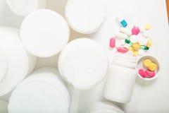 Olikt preventivpillerar och kapselställe i behållare Royaltyfri Bild