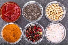 Olikt torka kryddor, såser och sädesslag i glass former på backgro Arkivbilder