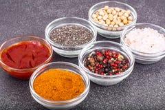 Olikt torka kryddor, såser och sädesslag i glass former på backgro Arkivfoto