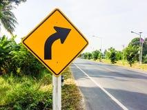 Olikt trafiktecken bredvid landsvägen Royaltyfri Foto