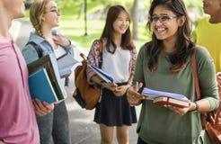 Olikt ungt begrepp för studentbok utomhus fotografering för bildbyråer