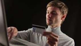 Oline που ψωνίζει πληρώνοντας την πιστωτική κάρτα στο lap-top φιλμ μικρού μήκους