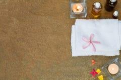 Olio aromatico, bruciato candela, fiori giallo arancione di rosa, asciugamano bianco sul fondo d'annata della pietra di lerciume Fotografie Stock Libere da Diritti