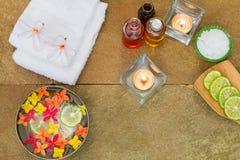 Olio aromatico, bruciato candela, giallo di rosa, fiori arancio, calce affettata, asciugamano bianco sul fondo d'annata della pie Fotografia Stock Libera da Diritti