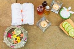 Olio aromatico, bruciato candela, giallo di rosa, fiori arancio, calce affettata, asciugamano bianco sul fondo d'annata della pie Fotografia Stock