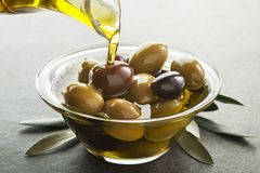 Olio d'oliva che versa alla fine della ciotola su fotografia stock libera da diritti