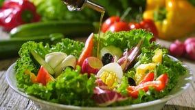 Olio d'oliva che versa sopra l'insalata mista stock footage
