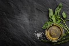 Olio d'oliva con differenti verdi sul lato destro della tavola di pietra nera Fotografia Stock