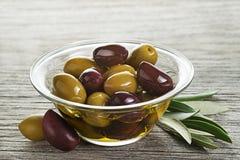Olio d'oliva con la frutta delle olive in ciotola di vetro fotografie stock libere da diritti
