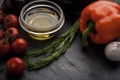 Olio d'oliva con la verdura differente e condimento sulla tavola di pietra nera Fotografie Stock