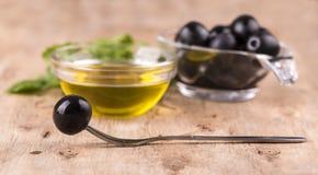 Olio d'oliva con le erbe e l'oliva fresche sulla forcella sul backgrou di legno Immagini Stock