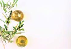 Olio d'oliva con un ramo delle olive verdi su fondo bianco immagine stock
