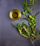 Olio d'oliva con un ramo delle olive verdi su fondo nero fotografie stock libere da diritti