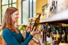 Olio d'oliva della bottiglia di esame della donna in supermercato Fotografie Stock