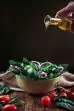 Olio d'oliva di versamento all'insalata degli spinaci Fotografia Stock