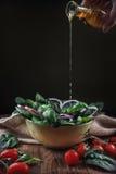 Olio d'oliva di versamento all'insalata degli spinaci Immagine Stock Libera da Diritti