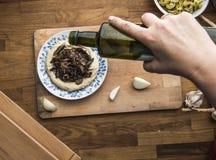 Olio d'oliva di versamento su un piatto del hummus del fungo, fondo di legno immagini stock libere da diritti