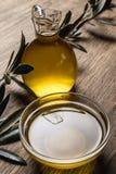 Olio d'oliva e foglie su una tavola di legno fotografia stock