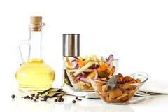 Olio d'oliva e funghi ed insalata marinati deliziosi in ciotole di vetro Immagine Stock