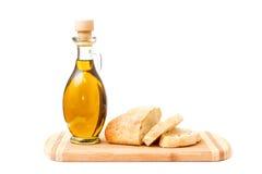 Olio d'oliva e pane affettato sul tagliere Fotografie Stock