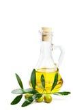Olio d'oliva e ramo con le olive su bianco immagini stock libere da diritti