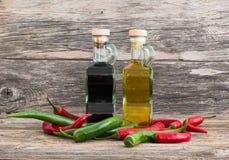 Olio d'oliva ed aceto in bottiglie di vetro con i peperoni freddi su fondo di legno immagine stock libera da diritti