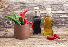 Olio d'oliva ed aceto in bottiglie di vetro, pepe freddo su vecchio fondo di legno modificato Fotografia Stock