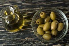 Olio d'oliva ed oliva sulla tavola di legno Fotografia Stock