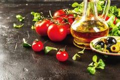 Olio d'oliva, foglie della lattuga, pomodori Immagini Stock
