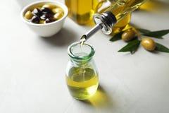 Olio d'oliva fresco di versamento nella bottiglia immagini stock