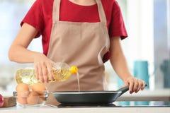 Olio da cucina di versamento della donna dalla bottiglia nella padella immagini stock libere da diritti