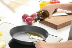 Olio da cucina di versamento della donna dalla bottiglia nella padella fotografie stock