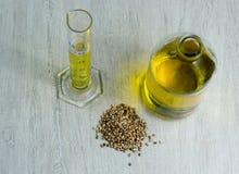 Olio di canapa in un barattolo ed in un becher di vetro immagine stock