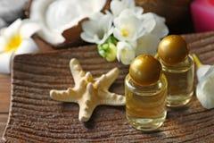 Olio di cocco in bottiglie, stelle marine e fiori Fotografia Stock