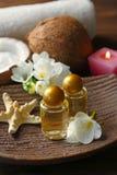 Olio di cocco in bottiglie, stelle marine e fiori Fotografie Stock
