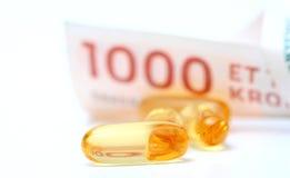 Olio di fegato di merluzzo Omega 3 capsule di gel con la banconota di valuta di 1000 corone scandinave danesi Fotografie Stock