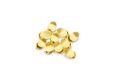 Olio di fegato di merluzzo Omega 3 capsule di gel o pils isolati su un fondo bianco Un gruppo di compresse trasparenti dell'olio  immagini stock