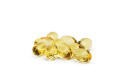 Olio di fegato di merluzzo Omega 3 capsule di gel o pils isolati su un fondo bianco Un gruppo di compresse trasparenti dell'olio  fotografia stock