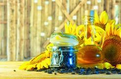 Olio di girasole circondato dalle inflorescenze del girasole sulla t Fotografia Stock Libera da Diritti