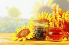 Olio di girasole e girasoli sulla tavola Immagine Stock