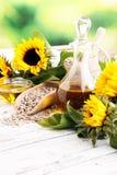 Olio di girasole, girasole e semi su legno fotografia stock