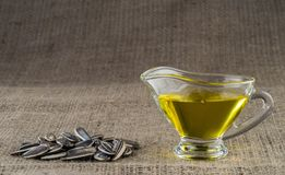 Olio di girasole in un crogiolo di sugo di vetro e una manciata di semi di girasole Fotografia Stock Libera da Diritti