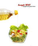 Olio di oliva che è versato sull'insalata. Immagini Stock