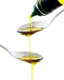 Olio di oliva che è versato in un cucchiaio Immagini Stock