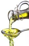 Olio di oliva che scorre dal carafe nel cucchiaio. fotografie stock