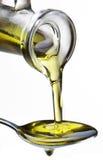 Olio di oliva che scorre dal carafe nel cucchiaio. fotografia stock