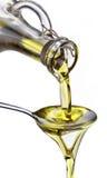 Olio di oliva che scorre dal carafe nel cucchiaio. immagine stock libera da diritti