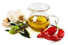 Olio di oliva con le olive, i peperoni e l'aglio immagini stock libere da diritti